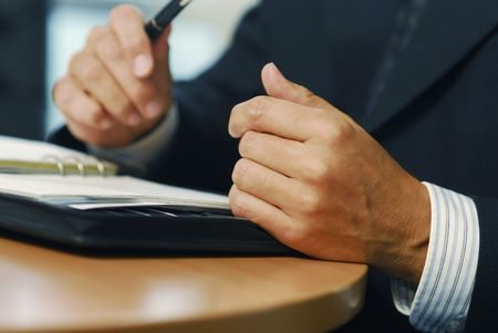 gesticulation: A businessman with pen doing gesticulation
