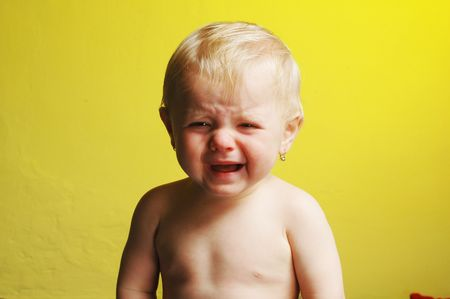A crying little child on yellow background Standard-Bild