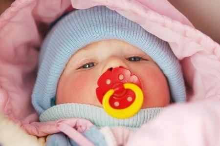 nursling: Baby with soother sleeping in pram