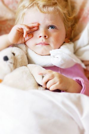 A sad girl with toy in bed Standard-Bild