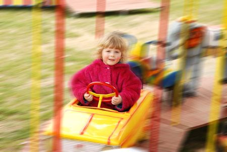 whirligig: A little girl sitting in a fair whirligig