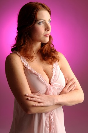 carroty: The young redhead attractive woman in nightshirt. Stock Photo