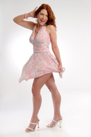 carroty: The young attractive redhead woman in pink dress. Stock Photo