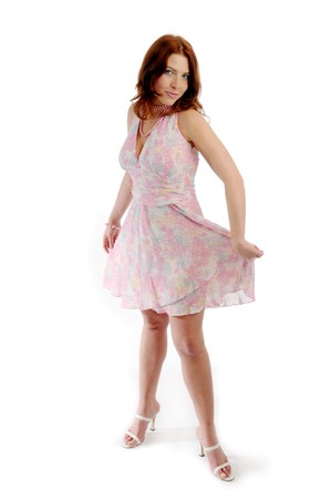 joyousness: The young attractive redhead woman in pink dress. Stock Photo