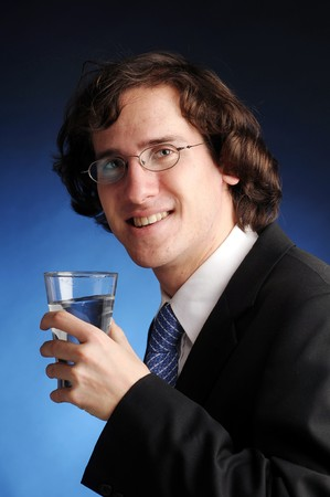 The portrait of young attractive businessman with glass of water. photo