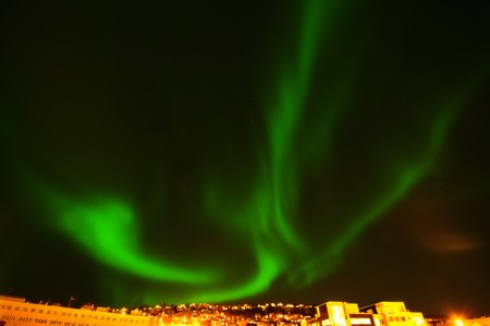 The green northern lights in Norwegian town Tromso. Stock Photo