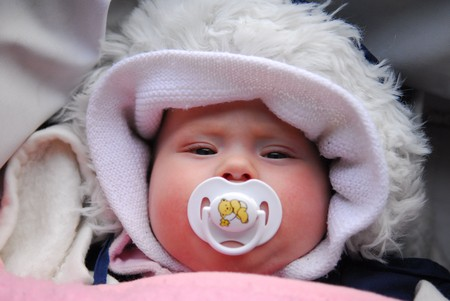 baby's dummies: The baby with pacifier in white cap in pram.