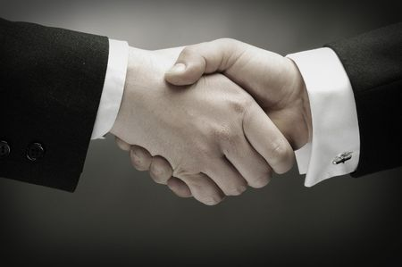 two hands: Two men in suits shaking hands.