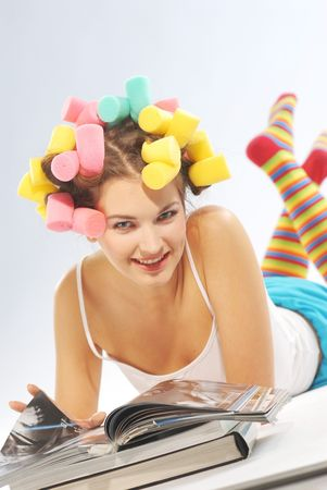 permanent wave: A woman with hair curlers and magazines.