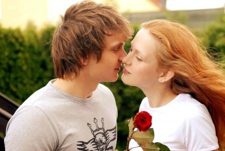 baiser amoureux: Young attractive heureux couple baiser � la rose Banque d'images