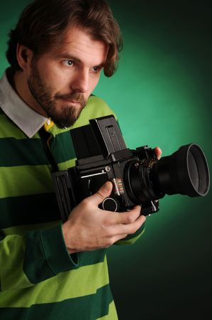 The attractive young photographer in green striped jersey with camera. Stock Photo - 5897818