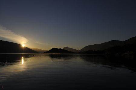 wavelet: The calm sea surface and hill silhouette during the sunset in Norge Stock Photo