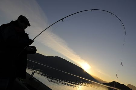 briny: The sillhouette of fisherman with rod during te sunset