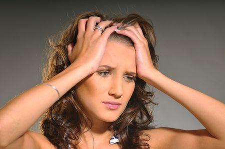 loose hair: Il ritratto di una donna attraente triste con i capelli sciolti ondulate su sfondo grigio