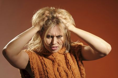 The sad woman with hand in her blond hair on brown background photo