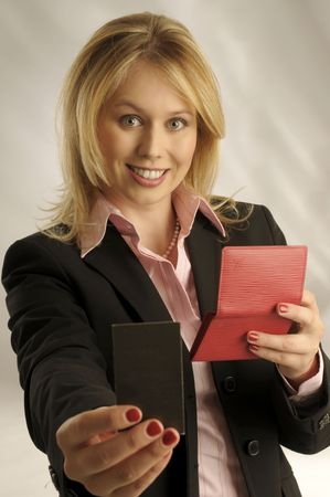 The attractive blond woman in black jacket with manager card and red wallet on gray background photo
