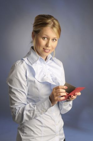 The beautiful blonde woman in blue shirt and with cards on gray background photo