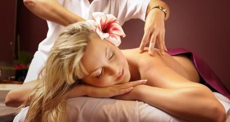 Die attraktive junge Frau mit Blume während der Thai-massage