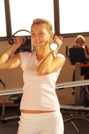 anaerobic: The young beautiful woman in white tee-shirt training in fitness centre