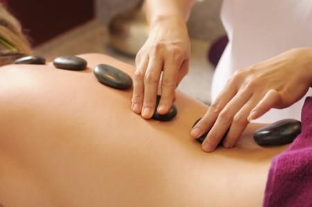 Die attraktive junge Frau mit Blume während der Thai-massage Standard-Bild