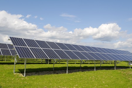 The black solar panels, green meadow and blue sky Stock Photo
