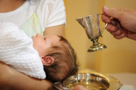 Die Taufe kleines Baby mit gesegnetes Wasser aus Eisen jug