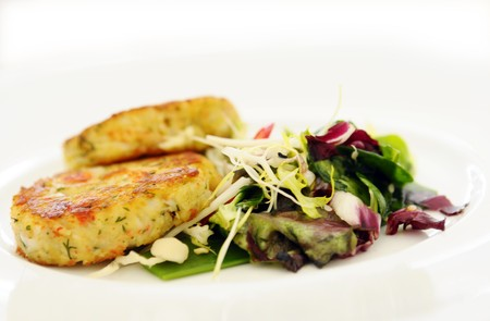 The crabs cakes with spring vegetables on white plate