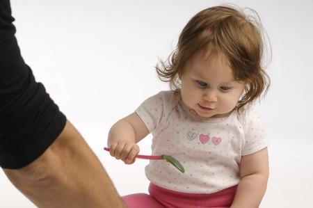 baby cutlery: Ni�a jugando con una cuchara