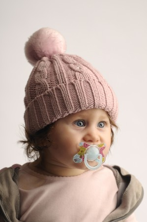 teat: portrait of a little girl in a hat and with a teat on gray background