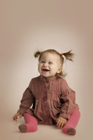 ittle: ittle girl with a ponytail on brown background