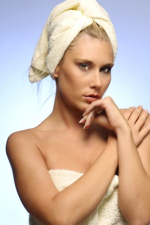Woman in the bath towel on blue-gray background photo