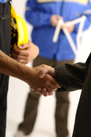 Handshake and one man in background