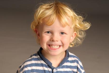 blonde boy: A little blonde boy grinning at camera