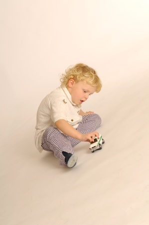 A little blonde boy playing with toy car photo