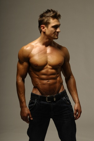 An attractive strong man posing in jeans