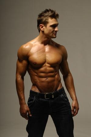 Eine attraktive starker Mann posiert in jeans