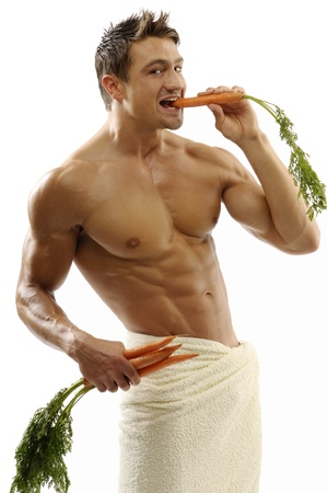 An attractive strong man wrapped in towel with carrots photo