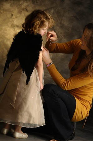 A little girl with mommy dressing her photo