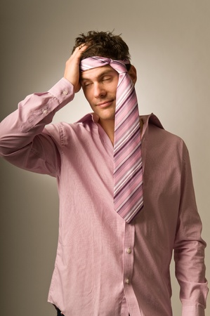 Man with tie around head and headache in morning photo