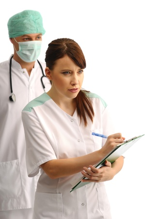 Doctor wearing cap and mask and young nurse writing\ notes