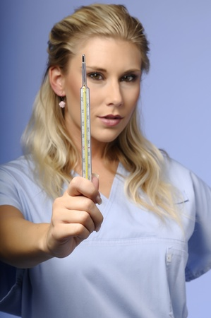 Portrait of blond girl holding thermometer photo