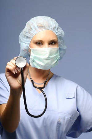 enfermera con cofia: Chica con una gorra de m�dicos y la m�scara de la celebraci�n de un estetoscopio