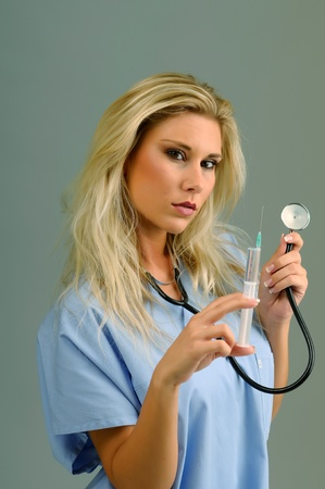 sexy nurse: Blond girl with an injection and stethoscope  Stock Photo