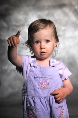 kid pointing: Picture of a pretty little girl pointing on something Stock Photo