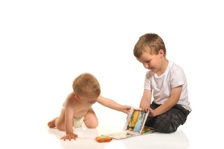 Two siblings reading a book together photo