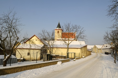 Snowy road going to the village with the church in Hrusice Stock Photo - 11000252