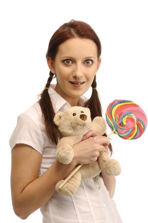Teenage girl with a lollipop and teddy bear photo