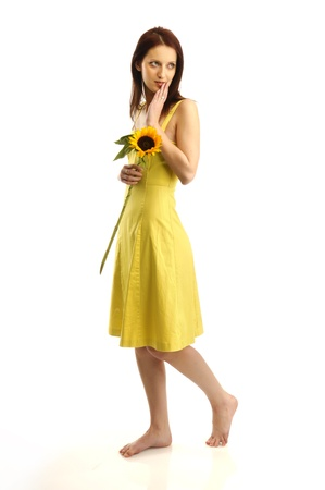 Young girl in yellov dress holding a sunflower photo