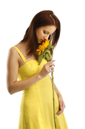 Young girl in yellov dress smelling a sunflower photo