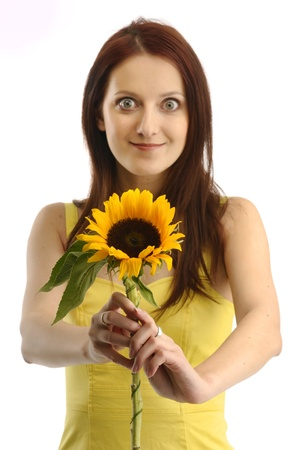 Portrait of a girl in yellov dress showing a sunflower photo